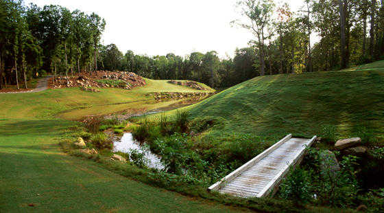 A sunny view with wooden bridge on the right at Neuse Golf Club