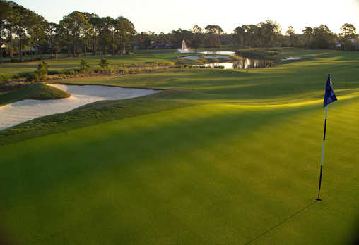 A view of a green with a bunker on the left side at West Course from Plantation Bay Golf and Country Club