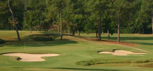 A view of a green protected by bunkers at Willow Brook Country Club