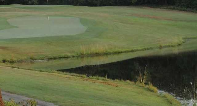 A view of a hole with water on the right at Pine Springs Golf Course