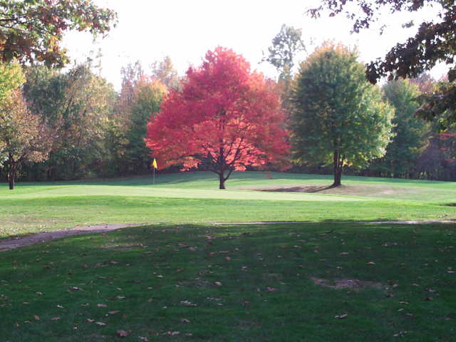 A view of a green guarded by fall red tree at English Hills Golf Course