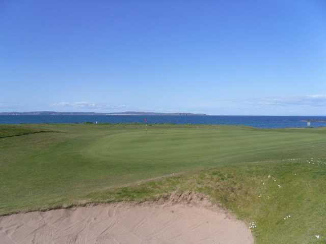 A view of green with water in background at Ballycastle Golf Club