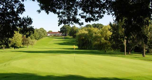 A sunny view of a green with clubhouse in background at South Herts Golf Club