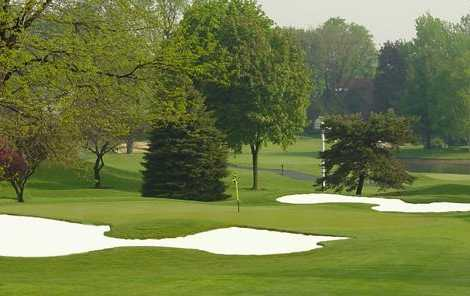 A view of a green protected by a collection of sand traps at Country Club of Lansing