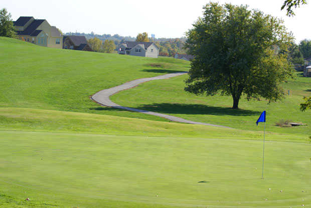 A view of a green with a cart path in background at River Oaks Golf Club