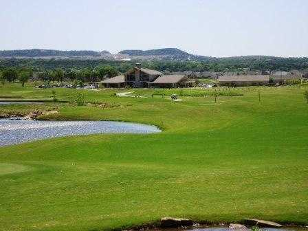 A view from a fairway with the clubhouse in the distance at Harbor Lakes Golf Club