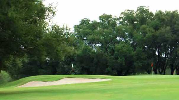 A view of a green guarded by a bunker at Starr Hollow Golf Club