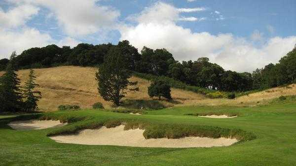 A view of a green surrounded by bunkers at Meadow Club
