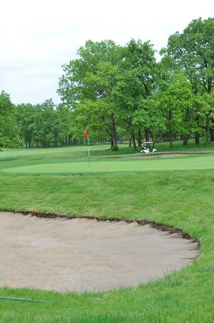 A view of a green protected by bunkers at Lake Valley Country Club