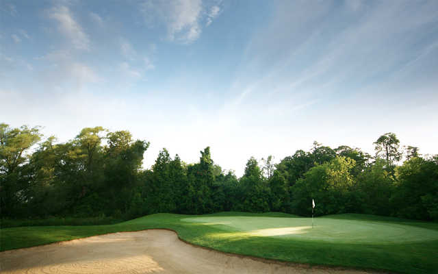 A view of a green guarded by a large bunker at Richmond Hill Golf Club