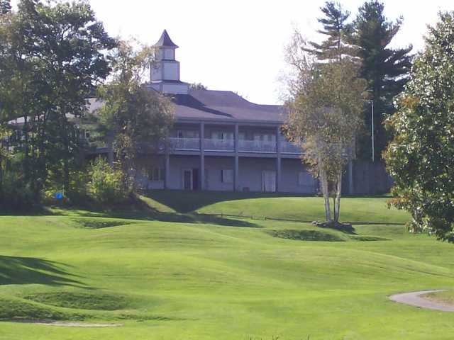 A sunny day view of a hole and the clubhouse at Windham Country Club