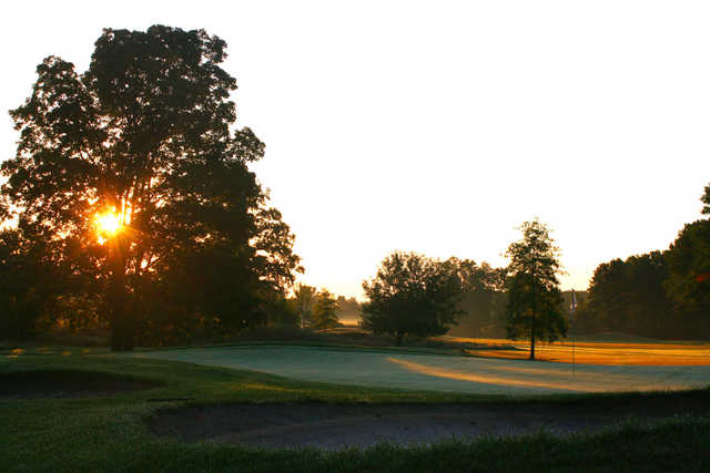 A sunset view of a green protected by bunkers at Brookshire Inn & Golf Club.