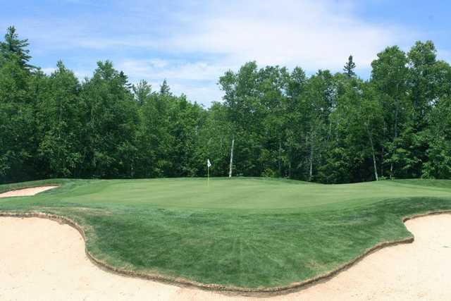 A view of hole #12 surrounded by an elegant bunker at Sugarloaf Golf Club