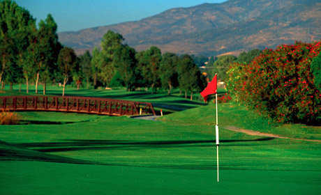 A green view from Chula Vista Golf Course with bridge in background