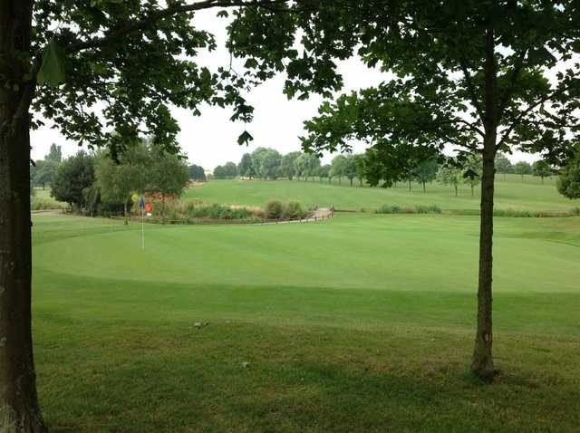 A view of the 10th green and surrounding trees at Windmill Village Golf Club