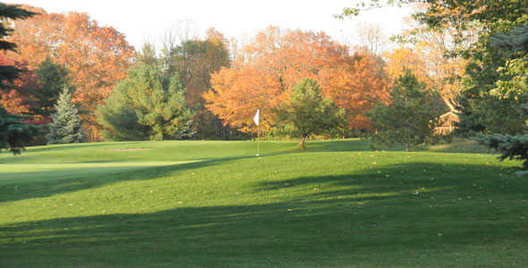 A fall day view of a green at Alpena Golf Club