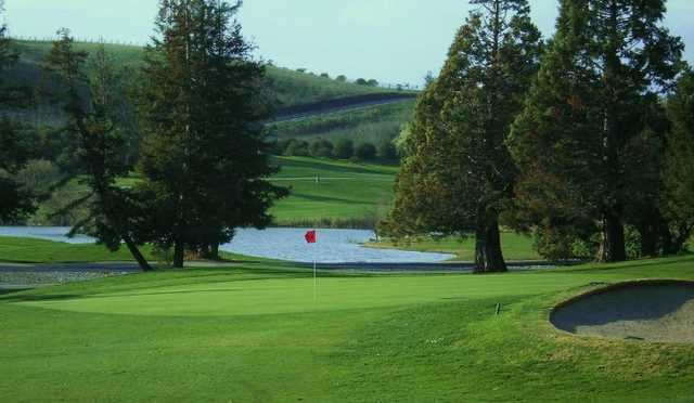 A view of green with bunker on the right and water in background at Summitpointe Golf Course