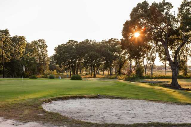 A sunny day view of a green protected by bunkers at Oak Creek Country Club.