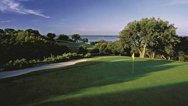 A sunny day view of a hole with water in the distance at White Bluff Golf Club.