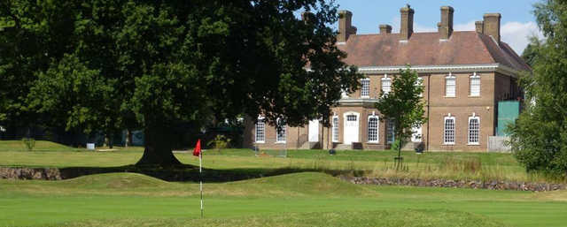 A view of a green and the clubhouse at Batchwood Golf & Tennis Centre.