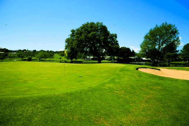 A sunny day view of a green at Riverhill Country Club.