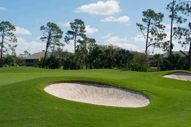 A sunny day view of a green protected by bunkers from The Club At Grandezza.