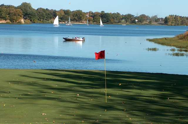 A sunny day view of a hole with water in background at Lake Shawnee Golf Course.