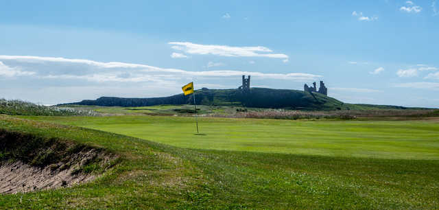 A sunny day view of a hole at Dunstanburgh Castle Golf Club.