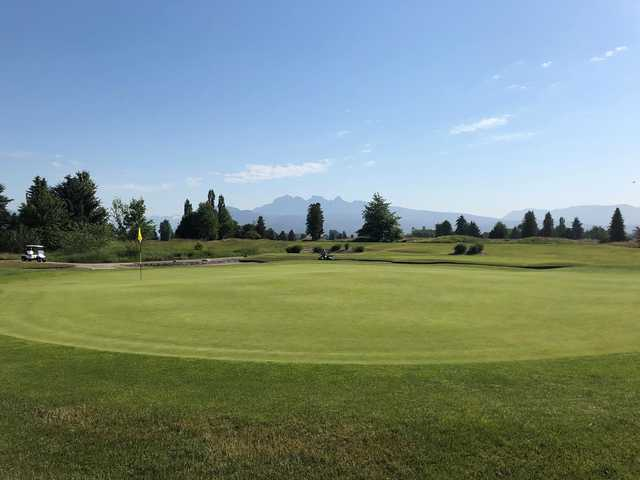 A sunny day view of a green at Meadow Gardens Golf Course.