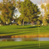 A view of a green with water in background at Shalimar Golf Club