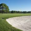 A view of a green protected by a large bunker at Eagles Golf Club