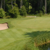 A view of a green guarded by a bunker and a pond at Wild Bluff Golf Course