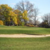 A view of a green protected by a bunker at Stone Ridge Golf Club