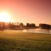 A sunset view of a green with water coming into play at Belfry Golf Club.