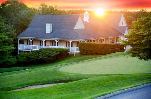 A sunset view of a green and the clubhouse at Woodholme Country Club.