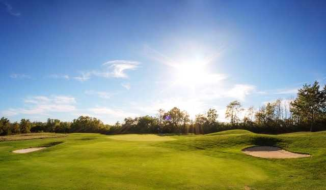A sunny day view of a green at Pipestone Golf Club.