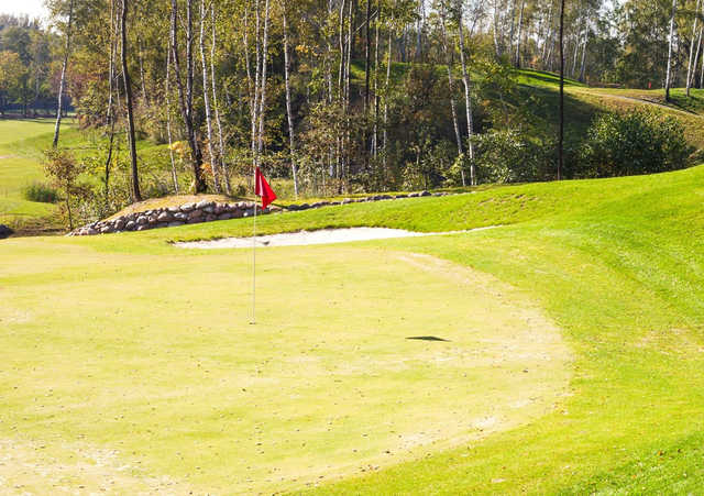 A sunny day view of a hole at Dunes West Golf Club.