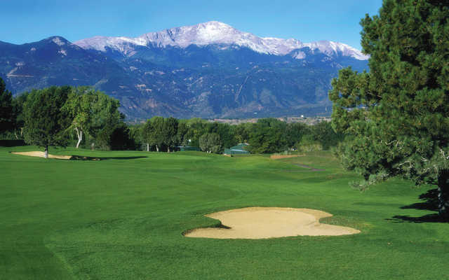 A view of a green with the mountains in the distance at Colorado Springs Country Club.