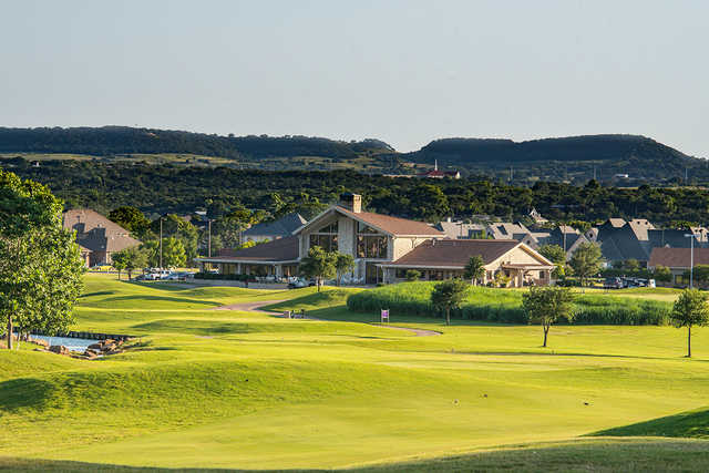 A view of a tee and the clubhouse at Harbor Lakes Golf Club.