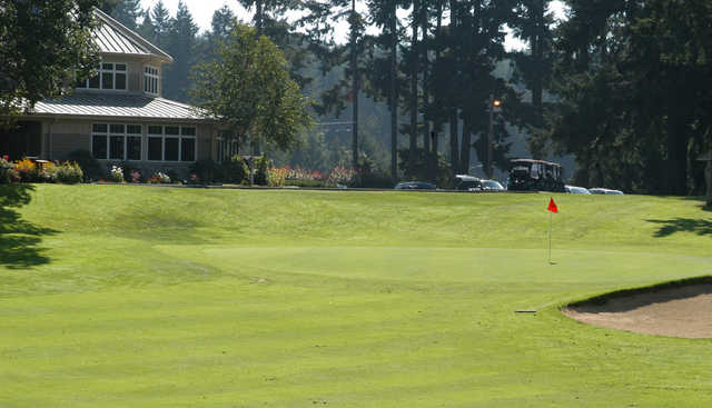 A sunny day view of a hole and the clubhouse at Eagles Pride Golf Course.