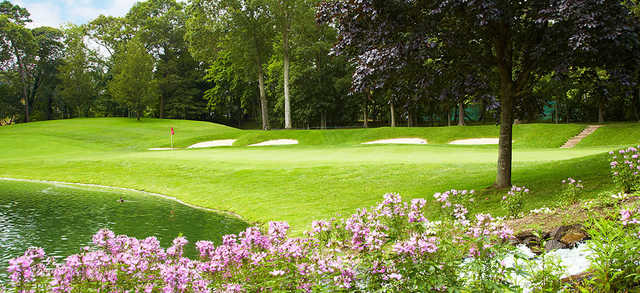 A view of a green surrounded by bunkers and flowers at Wind Watch Golf & Country Club..