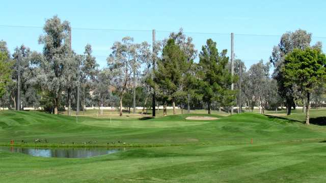 A sunny day view of a green at Augusta Ranch Golf Club.