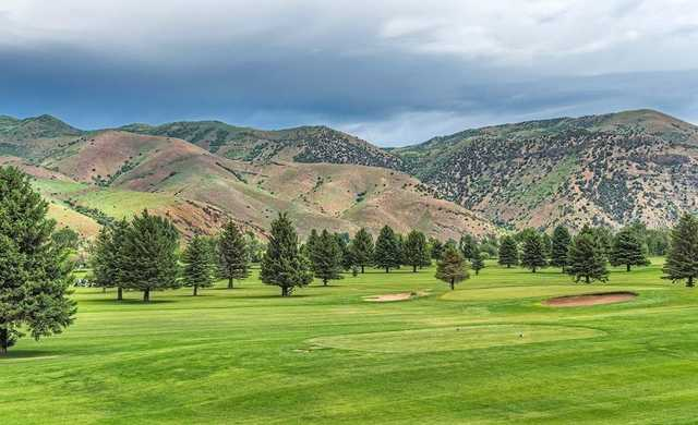 A view of a tee and a green in background at Round Valley Golf Course.