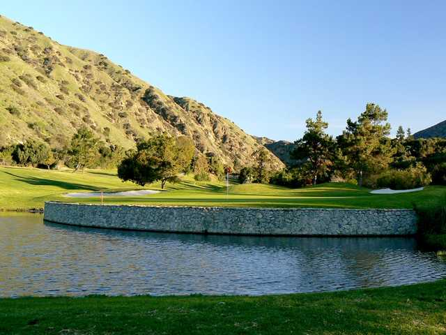 A view of a challenging green surrounded by water at San Dimas Canyon Golf Course.