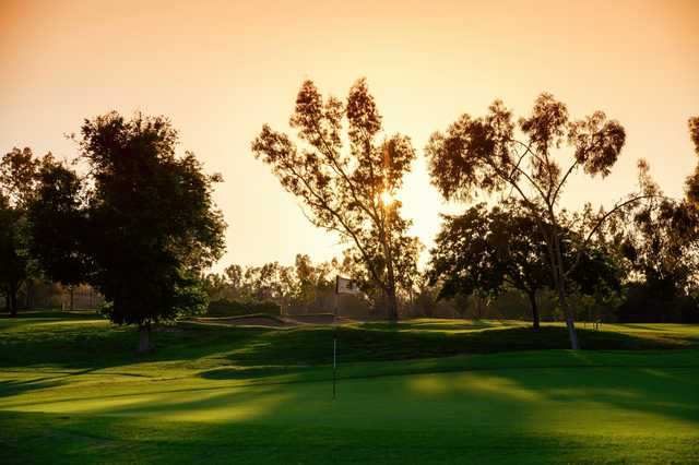 A sunset view of a green at Los Serranos Country Club.