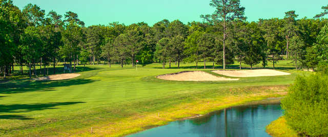 A view of a green surrounded by bunkers at Harbor Pines Golf Club.