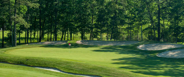 A view of a green protected by bunkers at Harbor Pines Golf Club.