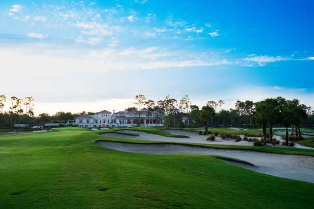 A view of a well protected green and the clubhouse from The Club At Mediterra.
