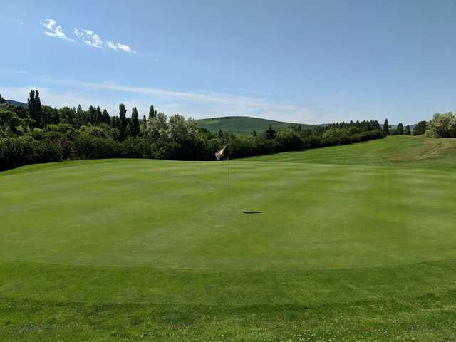 A sunny day view of a hole at University of Idaho Golf Course.