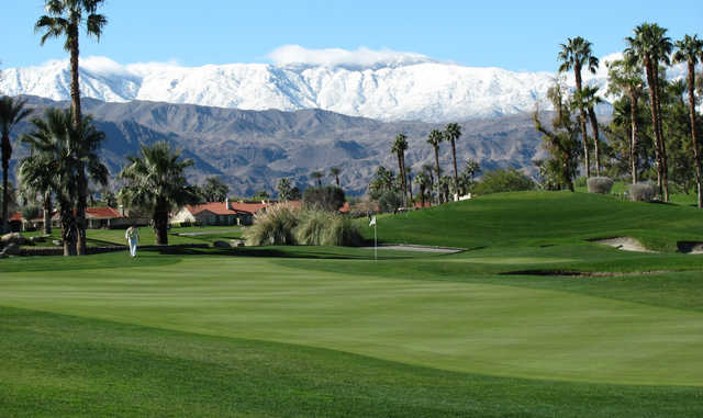 A view of a green and snowy mountains in background at Desert Falls Country Club.